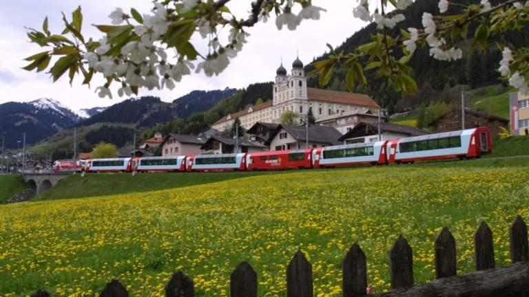 Der Glacier Express in Disentis mit Kloster im Hintregrund